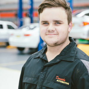 Blake from Daniels Automotive posing for a headshot photo at the workshop